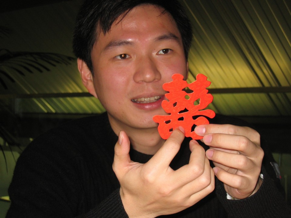 He is holding a Chinese symbol